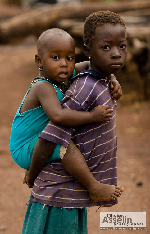 A girl carries a younger child on her back in the village of Nyologu, northern Ghana, on Wednesday June 6, 2007.