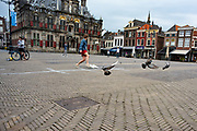 Playing football during the lockdown period on Markt square in the city Delft