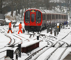 © Licensed to London News Pictures. 11/12/2017. Amersham, UK. Workmen walk past a stationary London Underground train surrounded by snow at Amersham Station in Buckinghamshire. Transport is being heavily affected across parts of the islands and southern England with British Airways cancelling 30 flights before 10am this morning. Photo credit: Tom Nicholson/LNP
