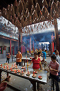 Cholon (Chinatown). Thien Hau Pagoda. Worshippers burning inscense. Spirals donated by visitors are suspended below the ceiling.
