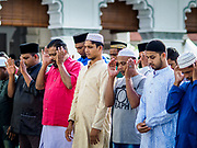 "22 AUGUST 2018 - GEORGE TOWN, PENANG, MALAYSIA: Men pray during Eid al-Adha services at Kapitan Keling Mosque in George Town. It is the oldest mosque in George Town. Eid al-Adha, ""Feast of the Sacrifice"" is the second of two Islamic holidays celebrated worldwide each year. It honors the willingness of Ibrahim (Abraham) to sacrifice his son as an act of obedience to God's command.     PHOTO BY JACK KURTZ"