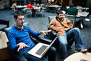 Kyle Eagan and William Adams discuss a class project with friends in the atrium of the Academic and Research Center on Ohio University's West Green. Photo by Ross Brinkerhoff