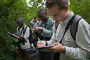 Simon Townsend, PhD student (University of St. Andrews) and field assistant Monday Gideon logging data of voice recordings from female chimpanzees (Pan troglodytes schweinfurthii). Budongo Forest Reserve, Masindi, Uganda, Africa.