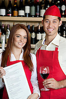 Portrait of young wait staff with wine glass and menu card in bar