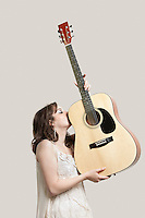 Young woman kissing guitar against gray background