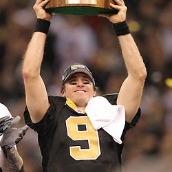 Jan 24, 2010; New Orleans, LA, USA; New Orleans Saints quarterback Drew Brees (9) holds up the NFC Championship trophy following an overtime victory over the Minnesota Vikings in the 2010 NFC Championship game at the Louisiana Superdome. Mandatory Credit: Derick E. Hingle-US PRESSWIRE