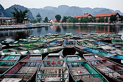 Barges moored along Tam Coc boat ride buildings complex, Ninh Binh Province, Vietnam, Southeast Asia