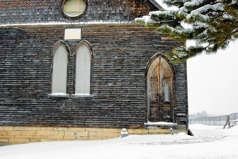 An abandoned Victorian Gothic church with a faded door in a snowstorm with the flakes going sideways...