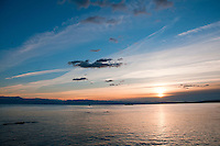 The sun sets over the Olympic Mountains and ocean from the breakwater in Victoria, BC