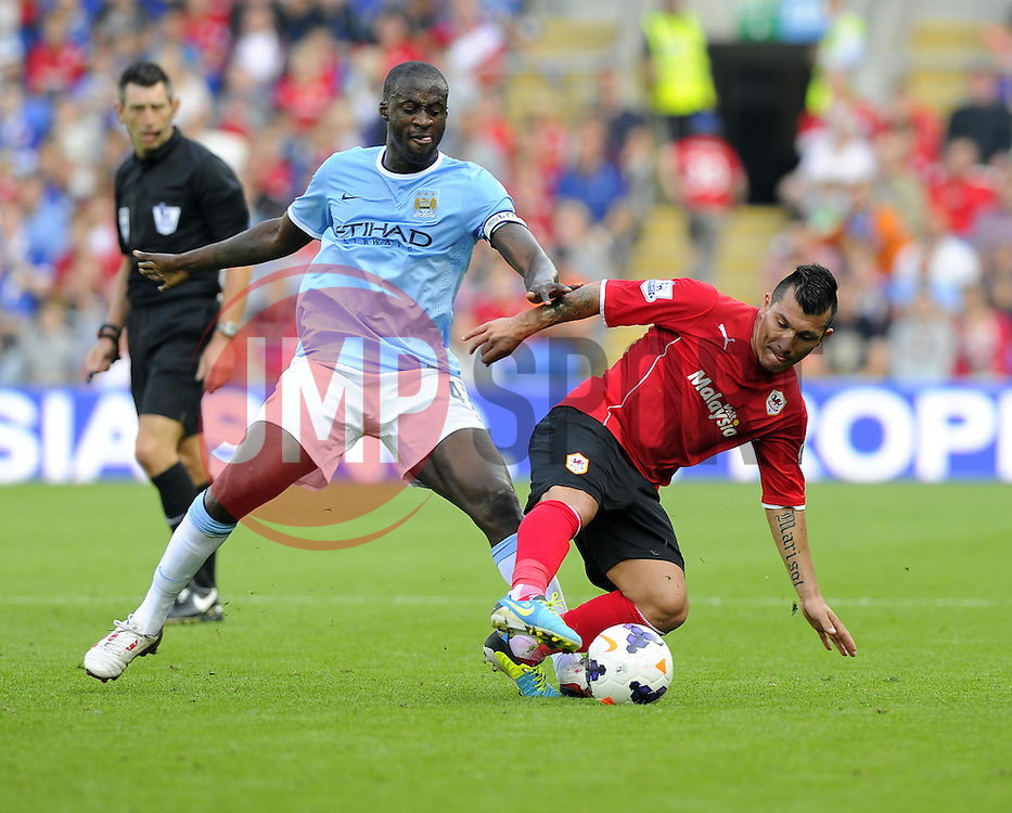 Manchester City's Yaya Touré battles for the ball with Cardiff City's Gary Medel  - Photo mandatory by-line: Joe Meredith/JMP - Tel: Mobile: 07966 386802 25/08/2013 - SPORT - FOOTBALL - Cardiff City Stadium - Cardiff -  Cardiff City V Manchester City - Barclays Premier League