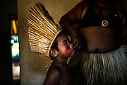 A Xerente indigenous boy receives red oil seed as preparation painting in his village near Tocantinia, Brazil, Friday, October 2, 2015.  One nearly empty vastness some decades ago, the northern part of Goias state territory, Tocantins was the latest Brazilian state to be created,  27 years ago. Now, luring Brazilians with an abundance of natural resources, its indigenous heritage, an aura of sustainability, infrastructure and lower prices, the government vows that this solid investment package will make up the facade of a land of opportunity. And eventually attract qualified workforce to populate the area. Profiting from side publicity of two world events, Brazil aims at throwing some light on its developmental potential, and has already helped to transform the locally known national indigenous games in the first international event of this type. In some weeks thousands of indigenous athletes from 24 countries will flock to the arena to compete, share and showcase their faces to the world.  (Hilaea Media/ Dado Galdieri for the Wall Street Journal)