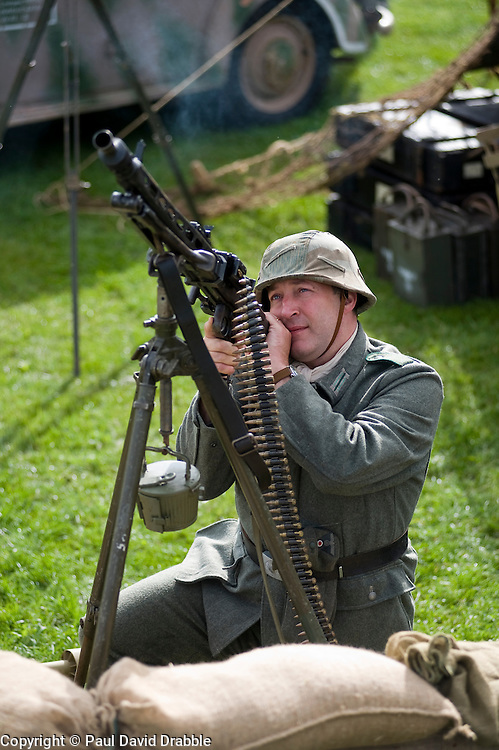 A reenactor dressed as a Panzergrenadier from the 21st Panzer Division living History group uses an MG42 mounted on an anti aircraft tripod at Croft Race Circuits Nostalgia Weekend August 2010. <br /> Images &copy; Paul David Drabble