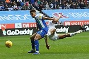 Leeds United midfielder Kemar Roofe (7) upended by Wigan Athletic defender Antonee Robinson (3) during the EFL Sky Bet Championship match between Wigan Athletic and Leeds United at the DW Stadium, Wigan, England on 4 November 2018.