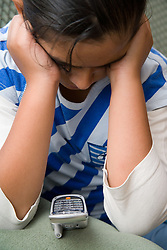 Upset child looking at mobile phone,