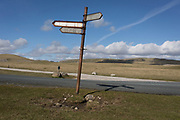 A leaning signpost pointing to Malham and Settle, in the Yorkshire Dales National Park on 12th April 2017, in Malham, Yorkshire, England.