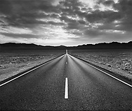 A blacktop desert highway and mountains at sunset, Death Valley National Park, California, USA