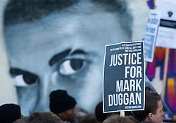 © London News Pictures. 11/01/2014. London, UK. A banner showing Mark Duggan's face at a vigil outside Tottenham Police Station in London, following a Coroners ruling of a lawful killing in the case of Mark Duggan earlier this week. Mark Duggan was hot dead by police in an incident that sparked riots across London and England.  Photo credit: Ben Cawthra/LNP