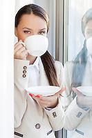 Portrait of businesswoman drinking coffee in office