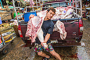 "26 SEPTEMBER 2012 - BANGKOK, THAILAND:  A man lifts a side of pork out of a truck to deliver it to a butcher shop in Khlong Toey Market in Bangkok. Khlong Toey (also called Khlong Toei) Market is one of the largest ""wet markets"" in Thailand. The market is located in the midst of one of Bangkok's largest slum areas and close to the city's original deep water port. Thousands of people live in the neighboring slum area. Thousands more shop in the sprawling market for fresh fruits and vegetables as well meat, fish and poultry.    PHOTO BY JACK KURTZ"