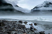 Fog flows down off Eagle Glacier covering the lake and framing the mountains and shoreline, in the Tongass National Forest north of Juneau, Alaska, April 21, 2017. <br /> Photo by David Lienemann