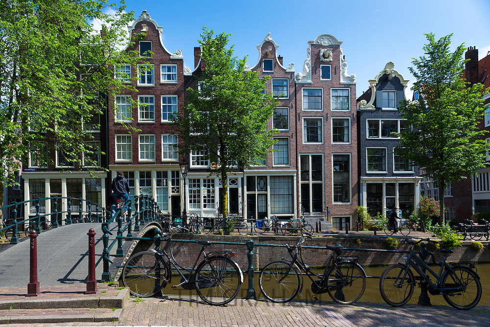Bicycles and canalside gabled houses - Dutch gables - Milkmaid's Bridge Melkmeisjesbrug on Brouwersgracht in Amsterdam, Holland