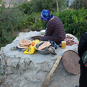 A schoolboy watches as bread is prepared in a stone oven, early in the morning, Turkmenistan