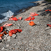 Discarded lifejackets on the on the beach near Skala Sykaminias in Lesbos island, Greece. Everyday hundreds of refugees, mainly from Syria and Afghanistan, are crossing in small overcrowded inflatable boats the 6 mile channel from the Turkish coast to the island of Lesbos in Greece. Many spend their life savings, over $1000, to buy a space on those boats.