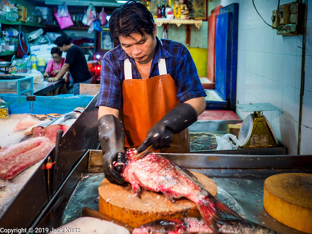 "26 FEBRUARY 2019 - BANGKOK, THAILAND: A fish monger cleans a fish for a customer in Bangkok's Chinatown. Bangkok has one of the largest ""Chinatown"" districts in the world. About 14% of all Thais have some Chinese ancestry and Chinese cultural practices are incorporated in many facets of Thai daily life.       PHOTO BY JACK KURTZ"