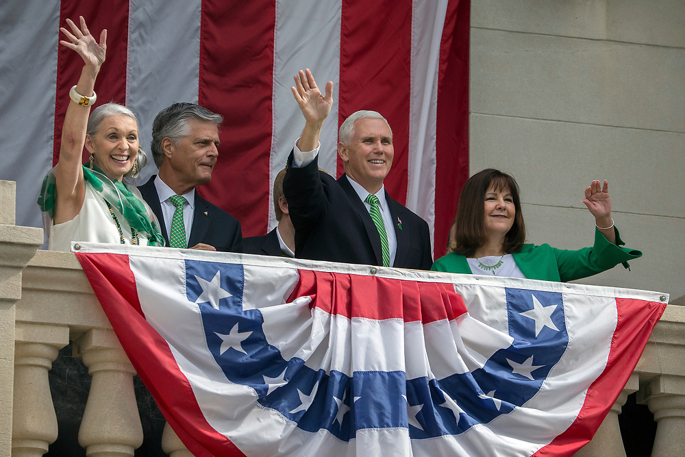 Vice President Mike Pence, center and his wife Karen Pence, right, are joined by Savannah Mayor Eddie DeLoach, second from the left, and his wife Cynthia DeLoach, left, as they wave from a balcony of City Hall, Saturday, March 17, 2018, during the St. Patrick's Day parade in Savannah, Ga. Irish immigrants to Savannah and their descendants have been celebrating St. Patrick's Day with a parade since 1824. (AP Photo/Stephen B. Morton)