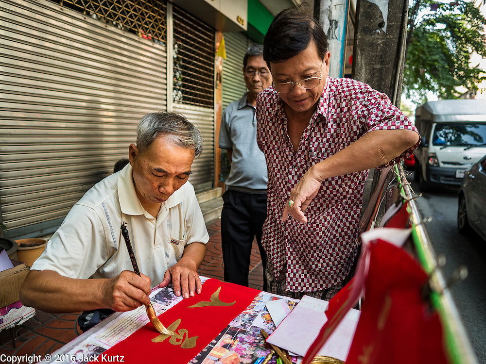 "03 FEBRUARY 2016 - BANGKOK, THAILAND:  People watch a traditional calligrapher write out New Year's greetings before Chinese New Year on Chareon Krung Road in Bangkok's Chinatown. Thailand has the largest overseas Chinese population in the world; about 14 percent of Thais are of Chinese ancestry and some Chinese holidays, especially Chinese New Year, are widely celebrated in Thailand. Chinese New Year, also called Lunar New Year or Tet (in Vietnamese communities) starts Monday February 8. The coming year will be the ""Year of the Monkey.""            PHOTO BY JACK KURTZ"
