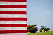 A John Deere tractor loaded with hay with the stars and stripes of the US Flag in the foreground set the stage for the annual barbeque hosted by Iowa Senator Tom Harkins.