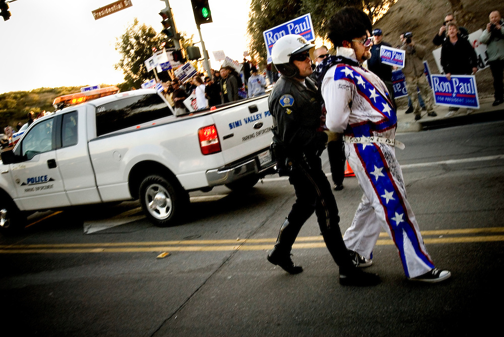 "Republican debate at Ronald Reagan Presidential Library in Simi Valley, California. A Ron Paul supporter dressed as Elvis is arrested after jaywalking. Other supporters scream ""Free Elvis"" as police officers handcuff him...Photographer Chris Maluszynski /MOMENT"