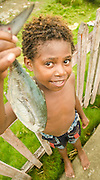 Young boy holds a fish caught traditionally in front of Lobo Village, Triton Bay, Papua.