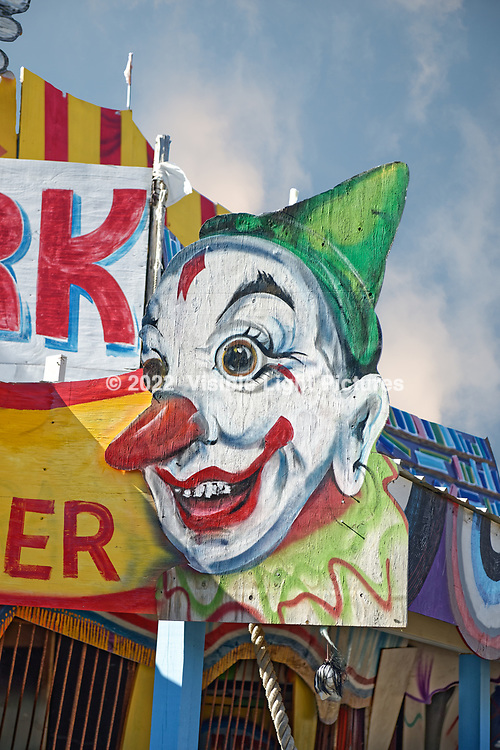 Creepy clown sign at a dilapidated, abandoned amusement park.