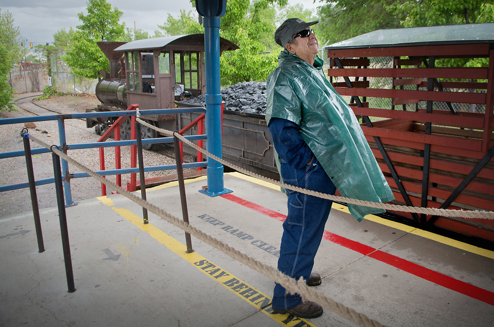mkb042517g/metro/Marla Brose --  ABQ BioPark's Rio Line train engineer Ernie Escalante takes shelter from the rain at the train depot at the Botanic Garden, Tuesday, April 25, 2017, in Albuquerque, N.M. The train, which runs Tuesday-Sunday in rain and shine, travels between the Zoo and the Aquarium and Botanic Garden. (Marla Brose/Albuquerque Journal)