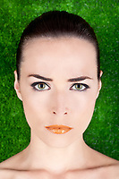 Closeup portrait of a serious angry beautiful woman with green eyes and glossy lips on green background