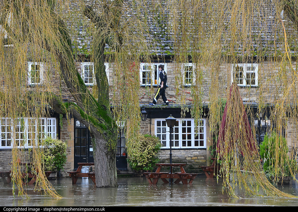 © Licensed to London News Pictures. 26/11/2012. Oxfordshire, UK A man is seen on the 1st floor roof of The Rose Revived public house is surrounded by the floodwater from the River Thames in Witney, Newbridge. Flooding on the River Thames today 26th November 2012 in Oxfordshire. Photo credit : Stephen Simpson/LNP