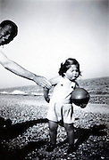father trying to get his child posing beach England 1940s