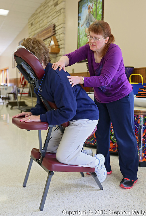 Ginny Henry (from left) of Marion receives a massage by Alison Schultz of Cedar Rapids during the Retreat & Refresh Stroke Camp at Camp Courageous in Monticello on Saturday, April 20, 2013. Henry is a caregiver for her husband.