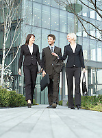 Three business people walking outside office building talking and smiling (surface view)