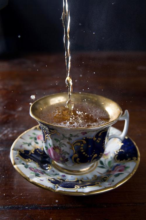 Pouring black tea into an antique English-style tea cup.