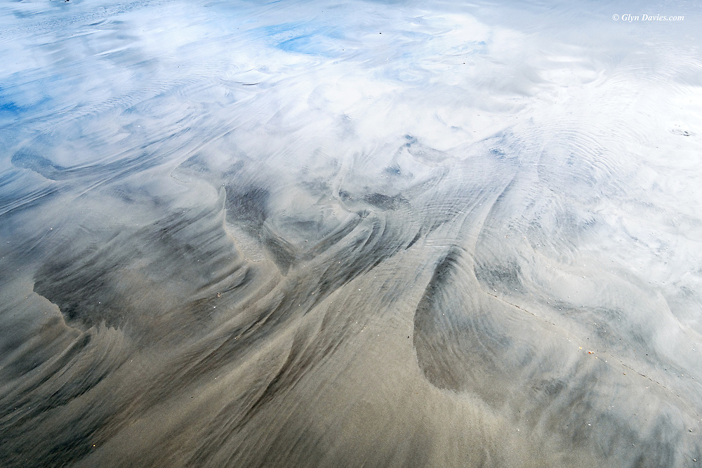 The most beautiful patterns caused by a sheen of water running over a wide expanse of sandy beach at Marazion, Cornwall.