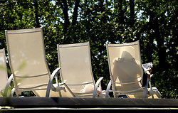 "SPA, BELGIUM - AUGUST-13-2005 -  A client relaxes outside in a lounge chair while reading a newspaper, under the lush green trees that surround Les Thermes de Spa. Health and beauty spas the world over, take their name from the original spa in Spa, Belgium where visitors have been coming for hundreds of years to "" take the waters "" at Les Thermes de Spa . (Photo © Jock Fistick)"