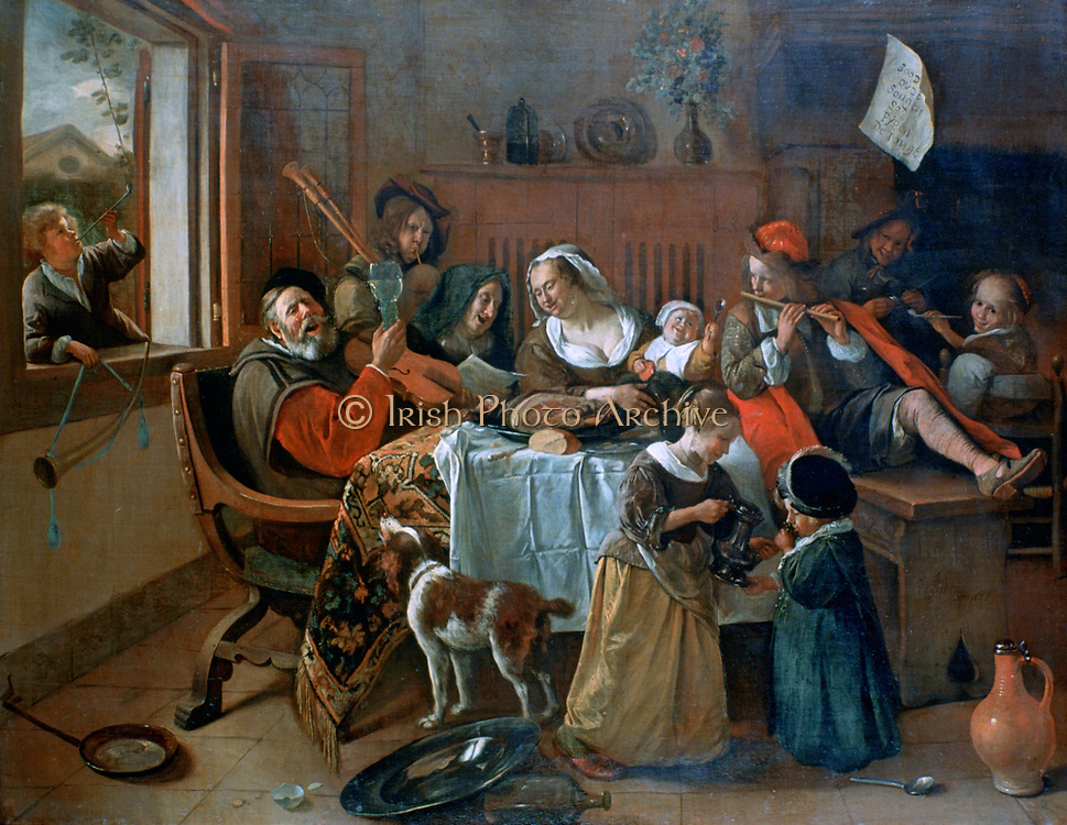 The Merry Family': Dutch interior showing a family making music round a table covered in  a carpet and a cloth with the remains of a meal.  Even the dog seems to be joining in.  The patriarch  puts his instrument aside and raises his glass in a toast. The women next him are singing from a sheet of music which the bagpiper behind them is following. Young man plays a flute and boy smoking a clay pipe in the window holds a horn.   Jan Steen (1626-1679) Dutch painter.