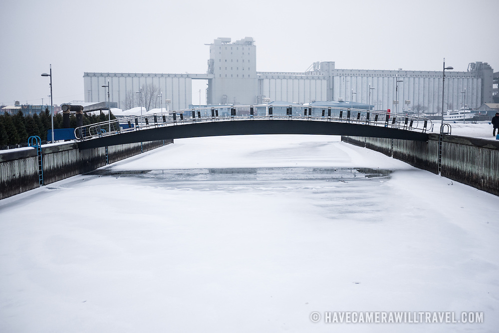 Frozen river in the middle of winter on Quebec City's waterfront, with a walking bridge over it.