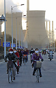 """Factory workers cycle home from a day's work at  """"Baogang"""", or Baotou Iron and Steel in northern China December 2, 2003. Baotou Iron & Steel Group, a Chinese state-owned steel producer, won rights to mine an iron ore"""