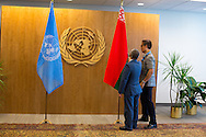 United Nations Protocol Assistant  Gavin Pan,  and Roderick Santos place the flag of Belarus, prior to President  Alyaksandr Lukashenka, entering the room.