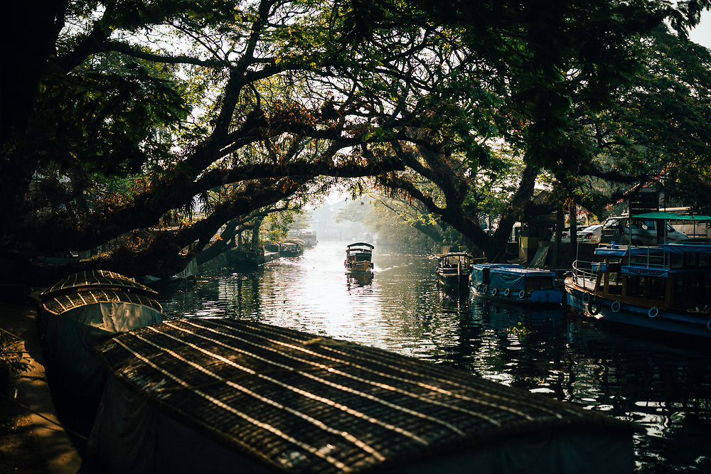 Alleppey, India -- February 19, 2018: Boats pass along a small canal in central Alleppey.