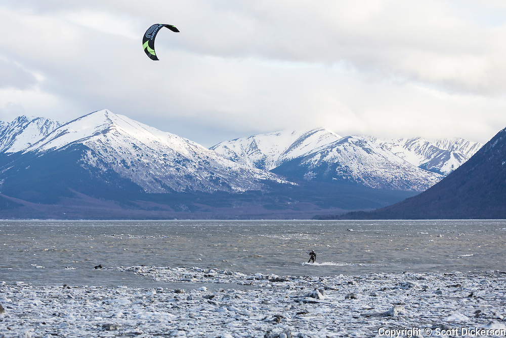 Tom Fredericks kiteboarding in Turnagain Arm, Alaska during the winter with ice packed against the shoreline.