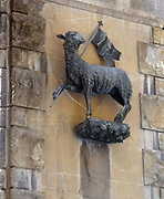 Statue detail on the outside of a church in Florence, Italy. Semi enclosed figurative statues such as this appear all over Florence. This is a statue of a sheep proudly holding a flag.